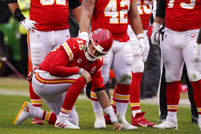 Kansas City Chiefs quarterback Patrick Mahomes kneels on the field after getting injured during the second half of an NFL divisional round football game against the Cleveland Browns, Sunday, Jan. 17, 2021, in Kansas City. (AP Photo/Charlie Riedel)