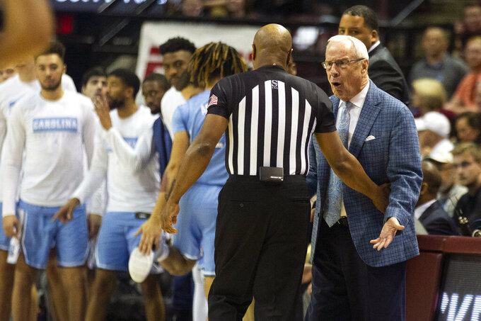 North Carolina head coach Roy Williams, right, disagrees with the referee in the first half of an NCAA college basketball game against Florida State in Tallahassee, Fla., Monday, Feb. 3, 2020. (AP Photo/Mark Wallheiser)