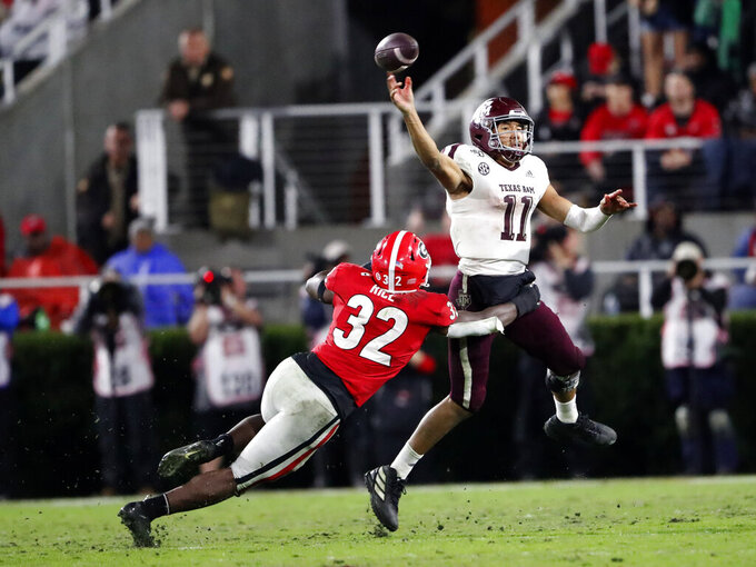 Texas A&M quarterback Kellen Mond (11) throws under pressure from Georgia linebacker Monty Rice (32) in the second half of an NCAA college football game Saturday, Nov. 23, 2019, in Athens, Ga. Georgia won 19-13. (AP Photo/John Bazemore)