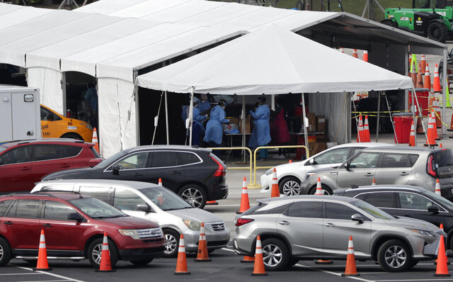 Lines of cars wait at a drive-through coronavirus testing site, Sunday, July 5, 2020, outside Hard Rock Stadium in Miami Gardens, Fla. Florida health officials say the state has reached a grim milestone: more than 200,000 people have tested positive for the novel coronavirus since the start of the outbreak. (AP Photo/Wilfredo Lee)