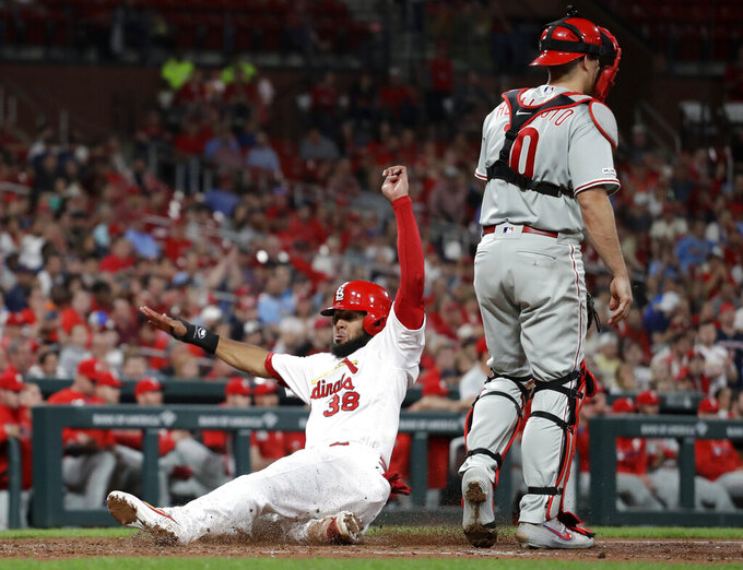 St. Louis Cardinals' Jose Martinez, left, scores past Philadelphia Phillies catcher J.T. Realmuto during the fifth inning of a baseball game Monday, May 6, 2019, in St. Louis. (AP Photo/Jeff Roberson)