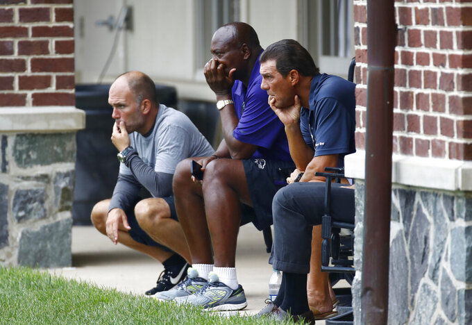 FILE - In this July 28, 2017 file photo, Baltimore Ravens assistant general manager Eric DeCosta, from left, general manager and executive vice president Ozzie Newsome and owner Stephen Bisciotti look out at practice fields during NFL football training camp in Owings Mills, Md. DeCosta is already hard at work in his new role as the Ravens' general manager, trying his best to make the transition from Newsome as seamless as possible. (AP Photo/Patrick Semansky, File)