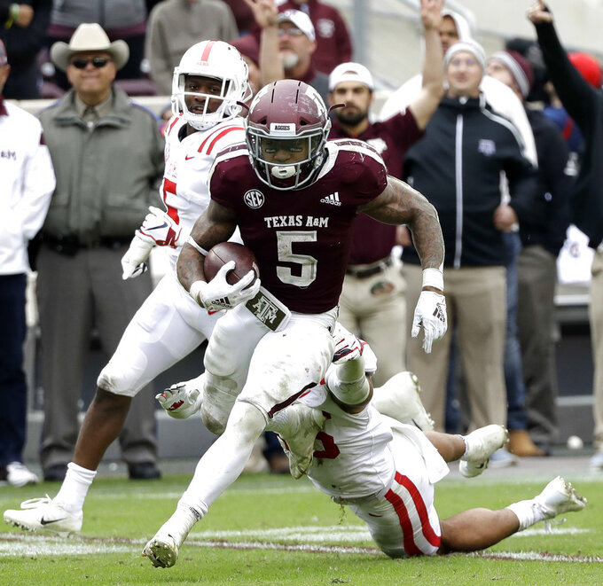 Texas A&M running back Trayveon Williams (5) breaks away from Mississippi linebacker Mohamed Sanogo, bottom, as he runs for a touchdown during the fourth quarter of an NCAA college football game Saturday, Nov. 10, 2018, in College Station, Texas. Texas A&M won 38-24. (AP Photo/David J. Phillip)
