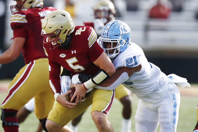 North Carolina linebacker Chazz Surratt (21) tries to strip the ball from Boston College quarterback Phil Jurkovec (5) during the first half of an NCAA college football game, Saturday, Oct. 3, 2020, in Boston. (AP Photo/Michael Dwyer)