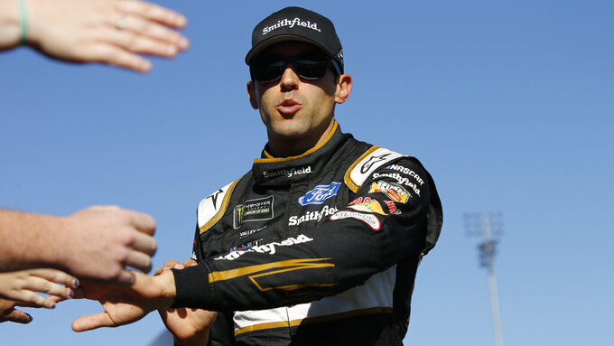 Aric Almirola greets fans during the NASCAR Cup Series race at Martinsville Speedway in Martinsville, Va., Sunday, Oct. 27, 2019. (AP Photo/Steve Helber)