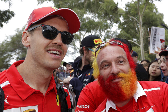 Ferrari driver Sebastian Vettel of Germany, left, poses with a fan as he arrives at the track of the Australian Grand Prix in Melbourne, Australia, Friday, March 15, 2019. The first race of the year is Sunday. (AP Photo/Rick Rycroft)