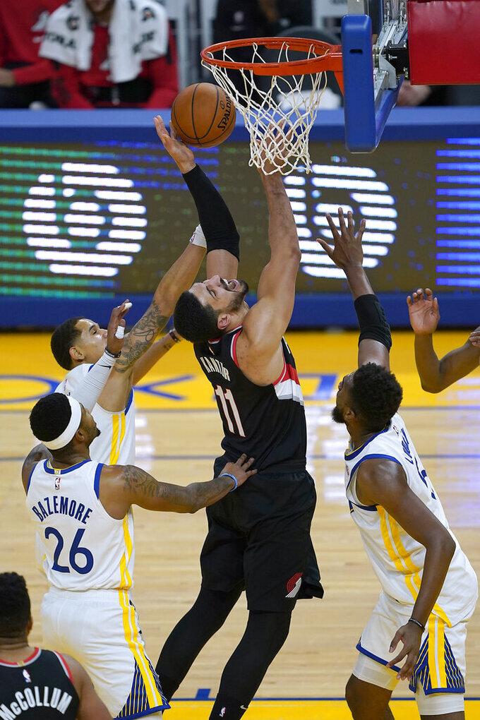 Portland Trail Blazers center Enes Kanter (11) reacts as he is fouled by Golden State Warriors forward Kevon Looney, right, during the first half of an NBA basketball game in San Francisco, Friday, Jan. 1, 2021. (AP Photo/Tony Avelar)