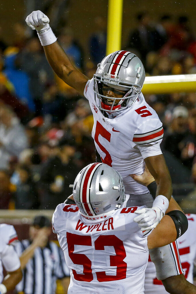 Ohio State wide receiver Garrett Wilson (5) celebrates in the arms of offensive lineman Luke Wypler (53) after scoring a touchdown against Minnesota during the third quarter of an NCAA college football game Thursday, Sept. 2, 2021, in Minneapolis. Ohio State won 45-31. (AP Photo/Bruce Kluckhohn)