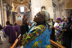 A woman prays during a Mass celebrated by Pope Francis for the Congolese community of Rome, in St. Peter's Basilica at the Vatican Sunday, Dec. 1, 2019. (AP Photo/Alessandra Tarantino)