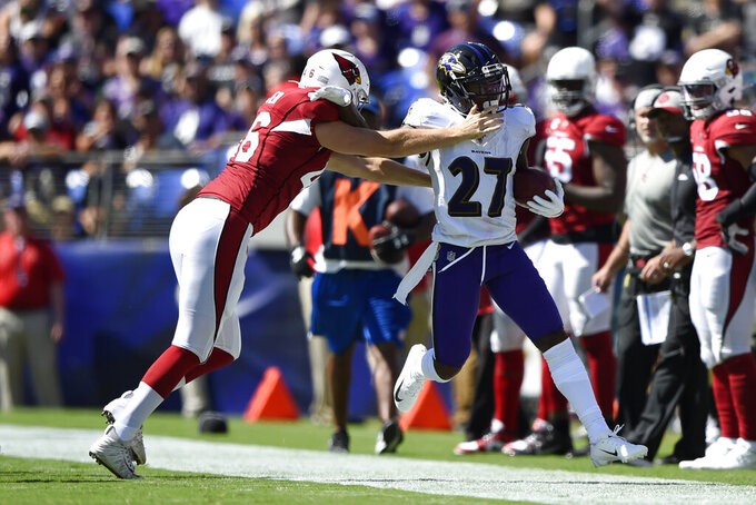 Baltimore Ravens' Cyrus Jones, right, rushes against Arizona Cardinals long snapper Aaron Brewer in the first half of an NFL football game, Sunday, Sept. 15, 2019, in Baltimore. (AP Photo/Gail Burton)
