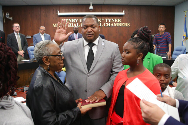 In this Oct. 15, 2019 file photo, Verona Tally, left holds the bible as Marty Small Sr., center, is sworn in as mayor of Atlantic City at Atlantic City Hall, in Atlantic City, N.J. Small, the incumbent who is seeking a 1-year term, is running in the Democratic primary against Pamela Thomas-Fields, a long-time city worker in the planning and economic development department, and James Whitehead, a Navy veteran and humanitarian aid organizer. (Edward Lea/The Press of Atlantic City via AP)