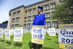 E. L. Meyers High School graduate Jose Sepulveda poses for family pictures while holding his graduation yard sign after picking it out from the others that were placed in front of the school, Tuesday May 19, 2020, in Wilkes-Barre, Pa., where the class of 2020 held a Virtual Graduation Ceremony. (Mark Moran/The Citizens' Voice via AP)