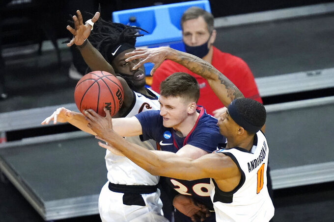 Oklahoma State guard Isaac Likekele, left, and teammate Avery Anderson III (0) pressure Liberty's Keegan McDowell during the second half of a first round NCAA college basketball game Friday, March 19, 2021, at the Indiana Farmers Coliseum in Indianapolis. Oklahoma State won 69-60. (AP Photo/Charles Rex Arbogast)