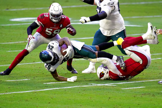 Philadelphia Eagles running back Miles Sanders (26) is tackled by Arizona Cardinals' linebacker Markus Golden as outside linebacker De'Vondre Campbell (59) looks on during the first half of an NFL football game, Sunday, Dec. 20, 2020, in Glendale, Ariz. (AP Photo/Ross D. Franklin)