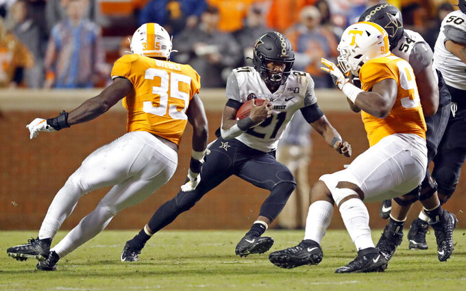 Vanderbilt running back Keyon Brooks (21) runs for yardage as he's chased by Tennessee linebacker Daniel Bituli (35) in the second half of an NCAA college football game against Tennessee, Saturday, Nov. 30, 2019, in Knoxville, Tenn. (AP Photo/Wade Payne)