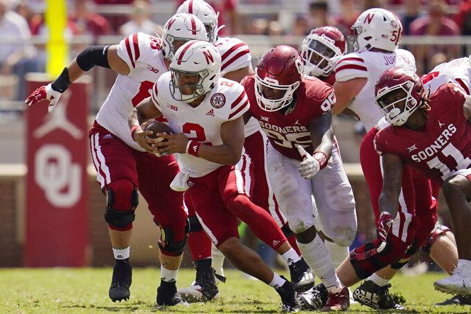 Nebraska quarterback Adrian Martinez (2) is pushed by Oklahoma defensive lineman Isaiah Thomas (95) and linebacker Nik Bonitto (11) in the second half of an NCAA college football game, Saturday, Sept. 18, 2021, in Norman, Okla. (AP Photo/Sue Ogrocki)