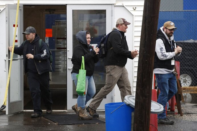 FILE -  In this April 3, 2020, file photo, workers rub their hands with hand sanitizer as they leave Bath Iron Works in Bath, Maine. Workers at one of the Navy's largest shipbuilders overwhelmingly voted to strike, rejecting Bath Iron Works' three-year contract offer Sunday, June 21 and threatening to further delay delivery of ships.   (AP Photo/Robert F. Bukaty, File)