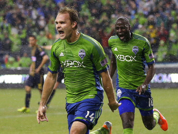 FILE - In this May 3, 2014, file photo, Seattle Sounders' Chad Marshall (14) celebrates with teammate Djimi Traore after Marshall scored the game-winning goal in the second half of an MLS soccer match against the Philadelphia Union, in Seattle. Three-time MLS defender of the year Chad Marshall has announced his retirement due to injury, bringing an end to a 16-year career that included stints with the Columbus Crew and Seattle Sounders. Marshall announced his decision Wednesday, May 22, 2019, after missing Seattle's last two games with knee inflammation. (AP Photo/Ted S. Warren, File)