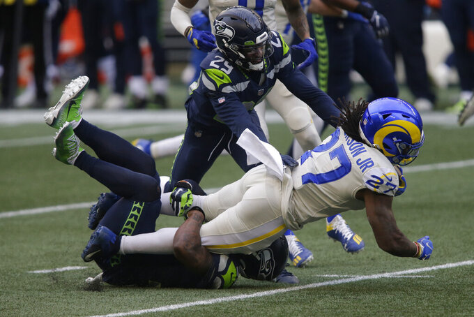 Los Angeles Rams running back Darrell Henderson Jr. (27) is tackled by Seattle Seahawks free safety D.J. Reed (29) and free safety Quandre Diggs (37), lower left, during the first half of an NFL football game, Sunday, Dec. 27, 2020, in Seattle. (AP Photo/Scott Eklund)