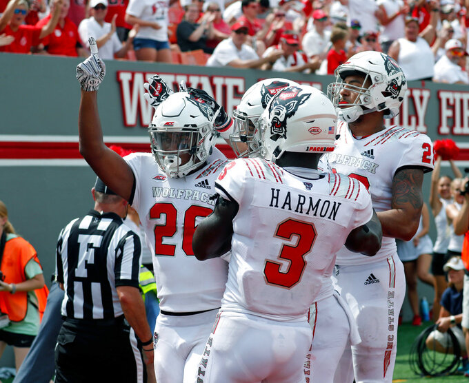 North Carolina State's Trent Pinnix (26) celebrates his touchdown with Kelvin Harmon (3) and other teammates after he scored during the second half of an NCAA college football game in Raleigh, N.C., Saturday, Sept. 8, 2018. (AP Photo/Chris Seward)