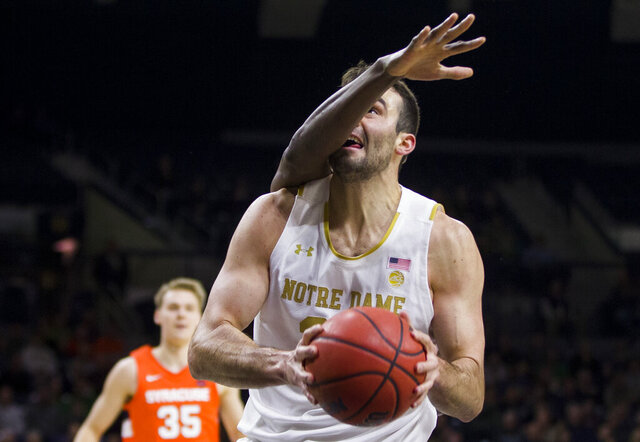 Notre Dame's John Mooney, front, looks for a shot as Syracuse's Bourama Sidibe (34) defends during the first half of an NCAA college basketball game Wednesday, Jan. 22, 2020, in South Bend, Ind. (AP Photo/Robert Franklin)