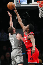 Toronto Raptors forward OG Anunoby (3) tips the ball away from Brooklyn Nets forward Joe Harris (12) during the first quarter of an NBA basketball game, Wednesday, Feb. 12, 2020, in New York. (AP Photo/Kathy Willens)