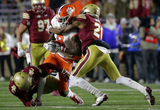 Boston College defensive back Lukas Denis (21) tackles Clemson wide receiver Justyn Ross (8) after Ross caught a pass during the first half of an NCAA college football game, Saturday, Nov. 10, 2018, in Boston. (AP Photo/Elise Amendola)