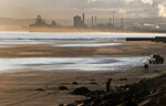 Workers on the beach in Hartlepool, England, Tuesday, Nov. 12, 2019 are backdropped by the Redcar steel plant that was shut down in 2015 and will be demolished. Political parties in Britain's Brexit-dominated December election are battling to win working-class former industrial towns, where voters could hold the key to the prime minister's office. The English port town of Hartlepool is an example. People there have long felt ignored by politicians in far-off London. (AP Photo/Frank Augstein)