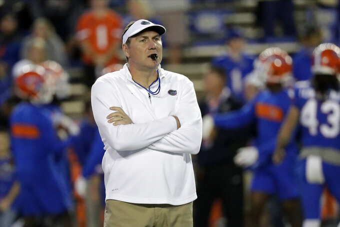 "FILE - In this Saturday, Nov. 30, 2019, file photo, Florida head coach Dan Mullen watches his players warm up before an NCAA college football game against Florida State, in Gainesville, Fla. Mullen is still wary about what lies ahead as Florida prepares to open the season at Ole Miss on Saturday, Sept. 26, 2020. ""Obviously, all the COVID stuff makes you anxious,"" Mullen said. (AP Photo/John Raoux, File)"