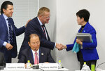 Tokyo Governor Yuriko Koike, right, shakes hands with IOC officials John Coates, center, and Christophe Dubi, left, during  their meeting in Tokyo Wednesday, Oct. 30, 2019.  Tokyo Governor Koike has told powerful IOC members she wants the Olympic marathon held in Tokyo and lashed out at what she called an