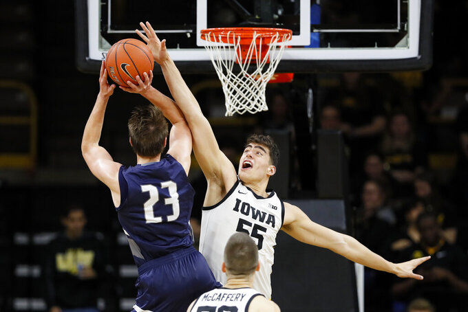 Iowa center Luka Garza (55) tries to block a shot by North Florida forward Carter Hendricksen (23) during the second half of an NCAA college basketball game, Thursday, Nov. 21, 2019, in Iowa City, Iowa. (AP Photo/Charlie Neibergall)