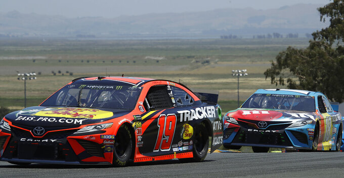 Martin Truex Jr. (19) leads Kyle Busch through a turn during a NASCAR Sprint Cup Series auto race Sunday, June 23, 2019, in Sonoma, Calif. (AP Photo/Ben Margot)