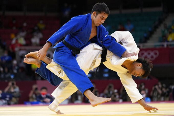 THIS CORRECTS TO GOLD, NOT BRONZE - Naohisa Takato of Japan, left, and Yang Yung-wei of Taiwan compete during their men's -60kg gold medal judo match at the 2020 Summer Olympics, Saturday, July 24, 2021, in Tokyo, Japan. (AP Photo/Vincent Thian)