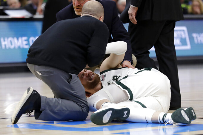 Medical personnel checks on Michigan State's Kyle Ahrens during the first half of an NCAA college basketball championship game against Michigan in the Big Ten Conference tournament, Sunday, March 17, 2019, in Chicago. (AP Photo/Nam Y. Huh)