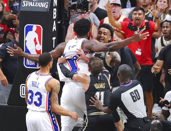Philadelphia 76ers Joel Embiid, top center left, is called for an offensive foul against Atlanta Hawks forward John Collins, who was called for a technical foul, as they break into an altercation while an official, Hawks' Trae Young (11) and 76ers' George Hill (33) move in to break it up during the fourth quarter of Game 6 of an NBA basketball Eastern Conference semifinal series Friday, Jun 18, 2021, in Atlanta. (Curtis Compton/Atlanta Journal-Constitution via AP)