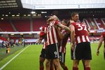 Sheffield United's Oliver McBurnie, left, celebrates with teammates his side's third goal during the English Premier League soccer match between Sheffield United and Tottenham Hotspur at Bramall Lane in Sheffield, England, Thursday, July 2, 2020. (Oli Scarff/Pool via AP)