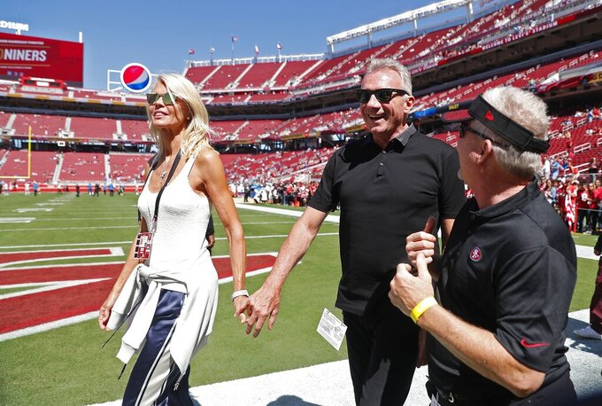 FILE - In this Sept. 16, 2018, file photo, Joe Montana and his wife, left, Jennifer walk onto the field at Levi's Stadium before an NFL football game between the San Francisco 49ers and the Detroit Lions in Santa Clara, Calif. Hall of Fame quarterback Joe Montana and his wife confronted a home intruder who attempted to kidnap their grandchild over the weekend, law enforcement confirmed on Sunday, Sept. 27, 2020.(AP Photo/Tony Avelar, File)