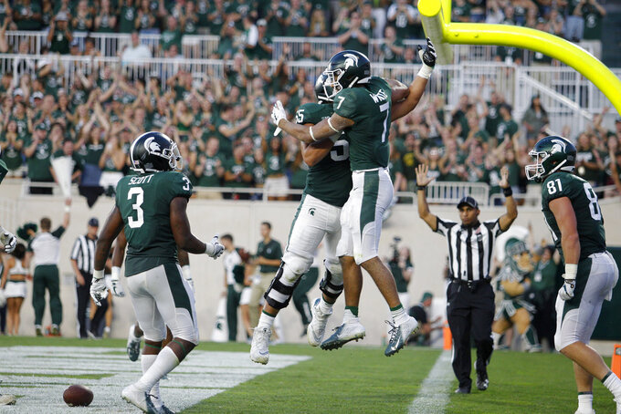 Michigan State's Cody White (7), LJ Scott (3), Matt Sokol (81) and Jordan Reid celebrate White's touchdown reception against Utah State during the second quarter of an NCAA college football game, Friday, Aug. 31, 2018, in East Lansing, Mich. (AP Photo/Al Goldis)