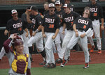The Oregon State bench celebrates behind Minnesota catcher Eli Wilson after Adley Rutschman hit a home run in the first inning against Minnesota in the opening game of an NCAA college baseball tournament super regional in Corvallis, Ore., Friday, June 8, 2018. (Mark Ylen/Albany Democrat-Herald via AP)