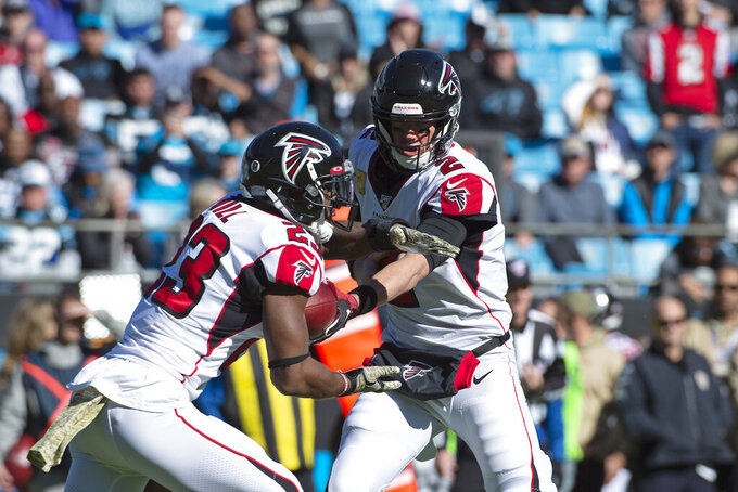 Atlanta Falcons quarterback Matt Ryan (2) hands off to running back Brian Hill (23) during the first half of an NFL football game against the Carolina Panthers in Charlotte, N.C., Sunday, Nov. 17, 2019. (AP Photo/Mike McCarn)