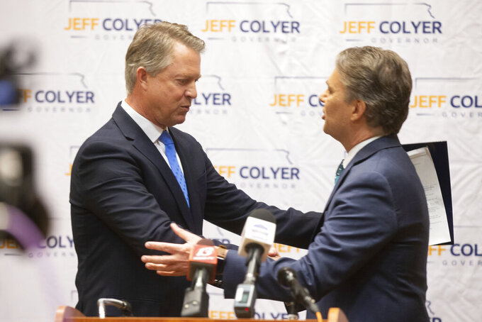 Former Gov. Jeff Colyer, right, hugs Sen. Roger Marshall, R-Kan., left, after Colyer's announcement for his governor candidacy and endorsement from Marshall at the Capitol Plaza Hotel in Topeka, Kan., on Monday, April 19, 2021. (Evert Nelson/The Topeka Capital-Journal via AP)