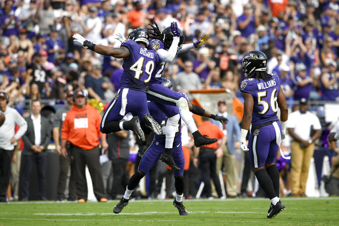 Baltimore Ravens cornerback Maurice Canady, center, celebrates his interception off a pass from Cleveland Browns quarterback Baker Mayfield, not visible, with linebacker Chris Board (49) and linebacker Tim Williams (56) during the first half of an NFL football game Sunday, Sept. 29, 2019, in Baltimore. (AP Photo/Nick Wass)