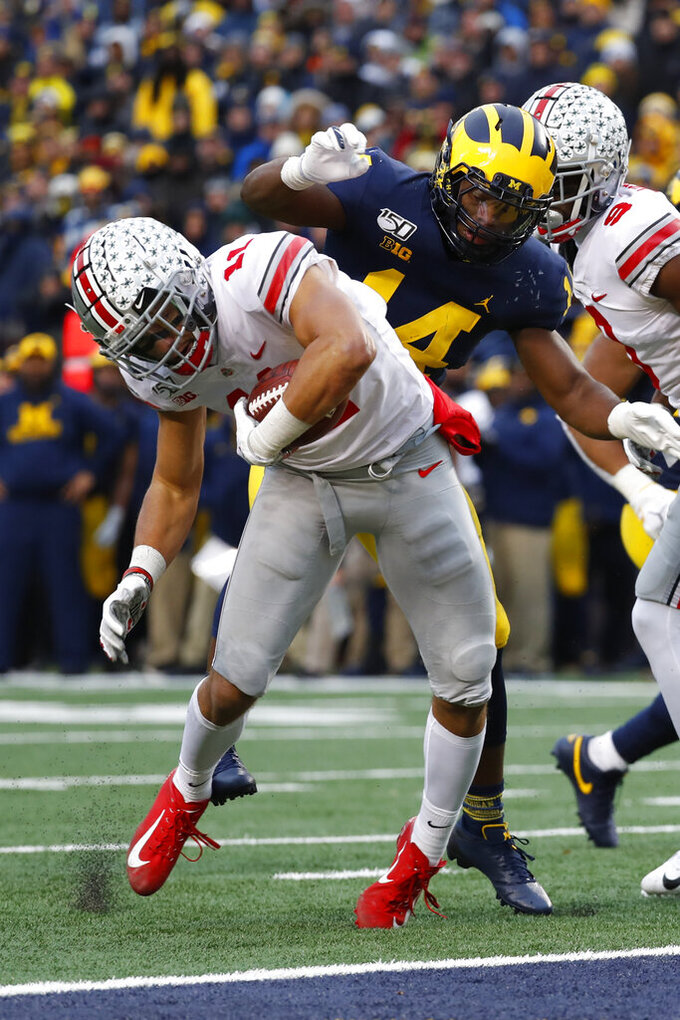 Ohio State wide receiver Austin Mack (11) scores on a 16-yard touchdown reception as Michigan defensive back Josh Metellus (14) defends in the second half of an NCAA college football game in Ann Arbor, Mich., Saturday, Nov. 30, 2019. (AP Photo/Paul Sancya)