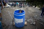 FILE - In this March 11, 2019 file photo, a little girl stands inside a plastic barrel while her family waits to collect water from an open pipe above the Guaire River, during rolling blackouts which has cut people off from running water in Caracas, Venezuela. President Nicolas Maduro, tries to project reassurance, saying the water supply is