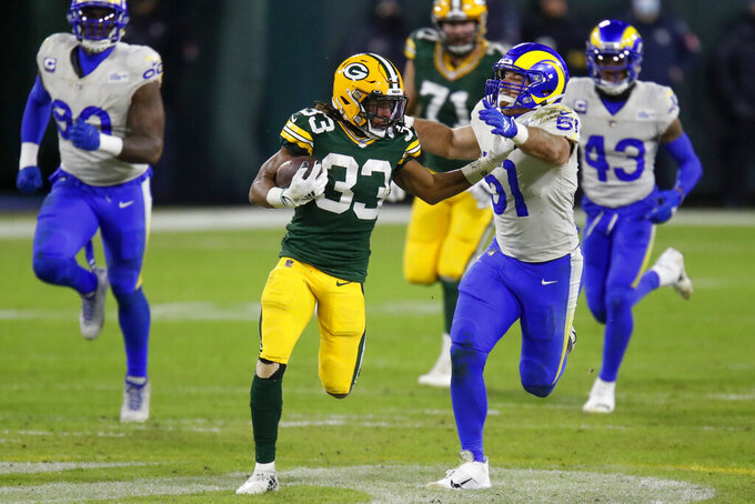 Green Bay Packers' Aaron Jones (33) breaks away from Los Angeles Rams' Troy Reeder (51) during the second half of an NFL divisional playoff football game Saturday, Jan. 16, 2021, in Green Bay, Wis. (AP Photo/Matt Ludtke)