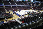 Ohio University basketball players warm up in an empty arena without fans before an NCAA college basketball game against Akron in the Mid-American Conference men's tournament, Thursday, March 12, 2020, in Cleveland. The Mid-American Conference tournament was cancelled Thursday, at an arena scheduled to be the site of NCAA men's tournament games next week .(AP Photo/Tony Dejak)