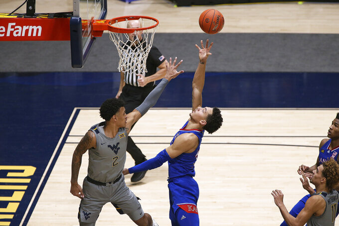 Kansas forward Jalen Wilson (10) shoots while defended by West Virginia forward Jalen Bridges (2) during the second half of an NCAA college basketball game Saturday, Feb. 6, 2021, in Morgantown, W.Va. (AP Photo/Kathleen Batten)