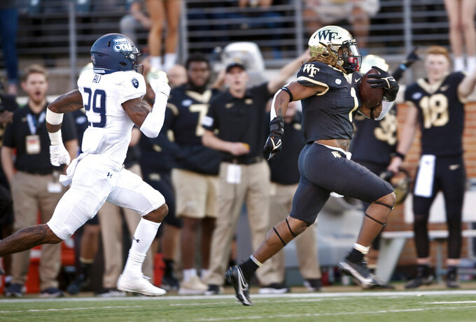 Wake Forest running back Christian Beal-Smith out runs Old Dominion's Ali Ali for a first-half touchdown during an NCAA college football game Friday, Sept. 3, 2021, in Winston-Salem, N.C. (Walt Unks/The Winston-Salem Journal via AP)
