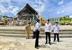 In this photo released by the Indonesian Presidential Palace, President Joko Widodo, second right, talks to an official as as he inspects an earthquake-damaged government building in Mamuju, West Sulawesi, Indonesia, Tuesday, Jan. 19, 2021. Widodo visited the areas where a deadly earthquake left thousands of people homeless in an effort to reassure them the government's response is reaching those struggling after the quake. (Indonesian Presidential Palace via AP)