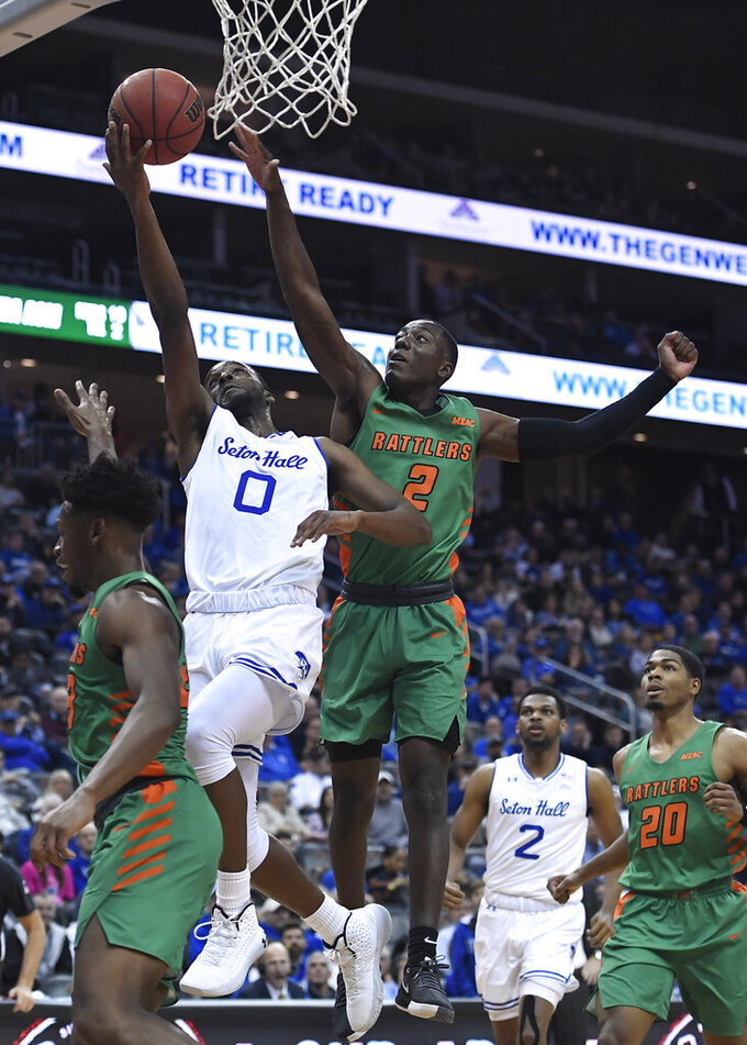 Seton Hall guard Quincy McKnight (0) attempts a layup as Florida A&M guard Kamron Reaves (2) defends during the second half of an NCAA college basketball game, Saturday, Nov. 23, 2019 in Newark, N.J. (AP Photo/Sarah Stier)